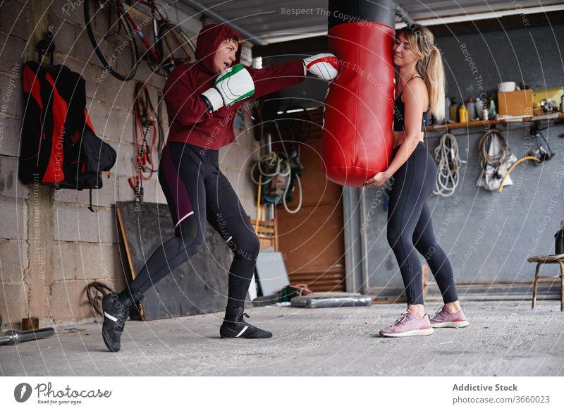 Boxsack für Sportlerinnen beim Boxtraining Boxer Boxsport Handschuh aufschlagen Kämpfer Fokus Bestimmen Sie Training intensiv Fitnessstudio Garage stark