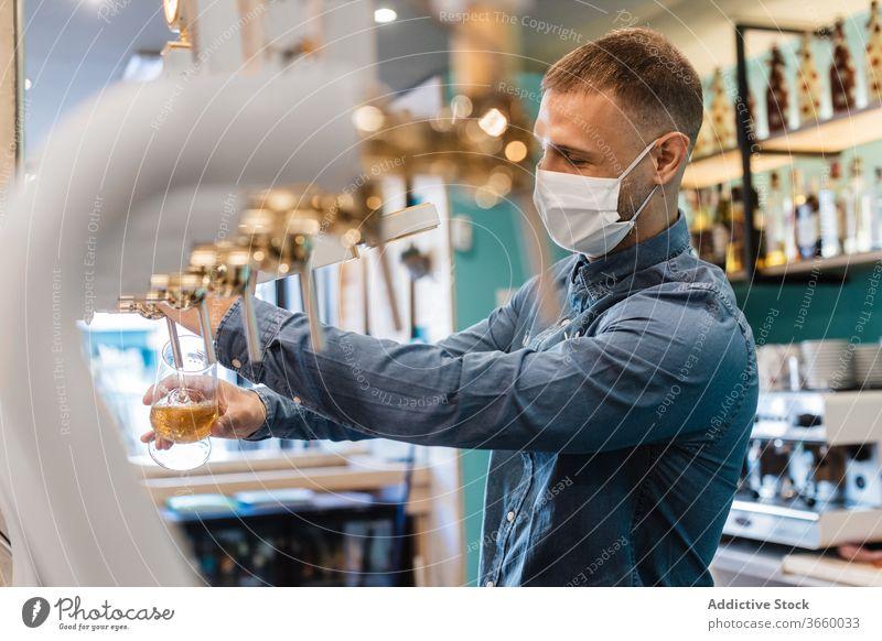 Junger Mann füllt Glas mit Bier für Kunde eingießen Wasserhahn frisch Barkeeper Mundschutz Pub Tiefgang Alkohol trinken Arbeit männlich jung Hemd positiv