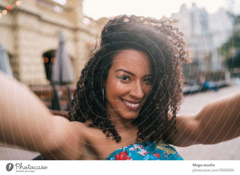 Afroamerikanische Frau, die sich in der Stadt ein Selfie gönnt. Großstadt Menschen Amerikaner Afro-Look Porträt Spaß cool Selbst Lächeln lockig Behaarung unter