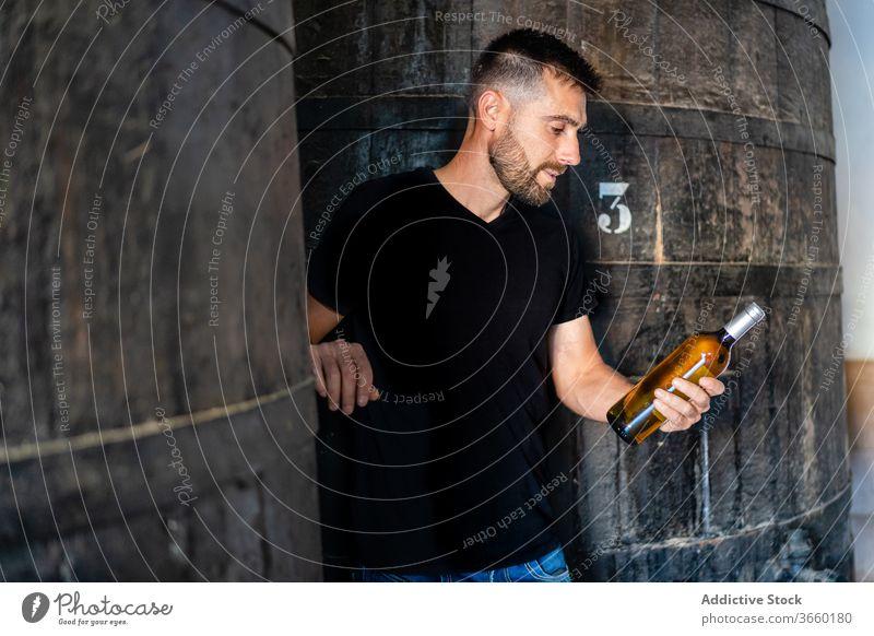 Winzer mit Weinflasche neben riesigem Holzfass Flasche prüfen positiv Lauf Weingut Fabrik Weinbau Weinherstellung Inszenierung Industrie Zeitgenosse