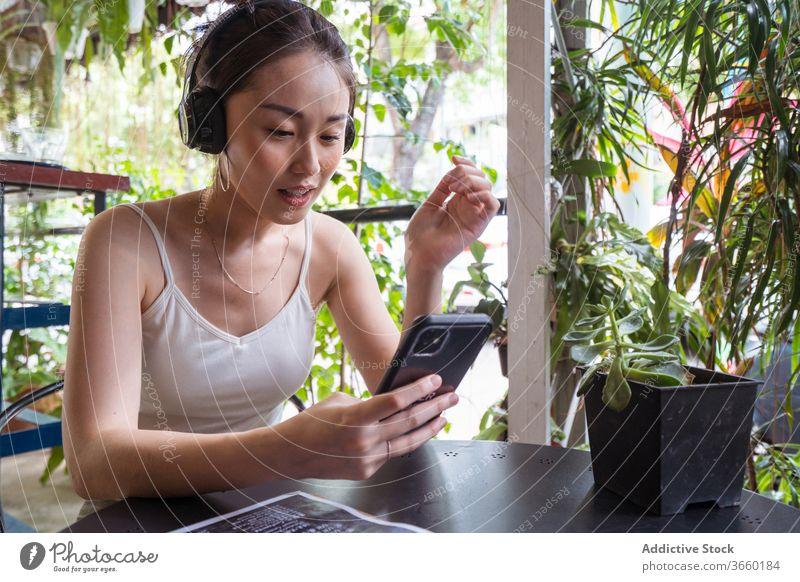 Asiatische Frau sieht Video auf Smartphone zuschauen lustig Kopfhörer genießen unterhalten benutzend Lächeln asiatisch ethnisch Sommer Apparatur jung Gerät
