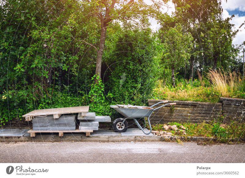 Schubkarre mit Fliesen auf einer Straße Projekt Straßenbelag Steine Kacheln stark solide Garten wohnbedingt heimwärts Verlegung Klotz Oberfläche grün Hinterhof
