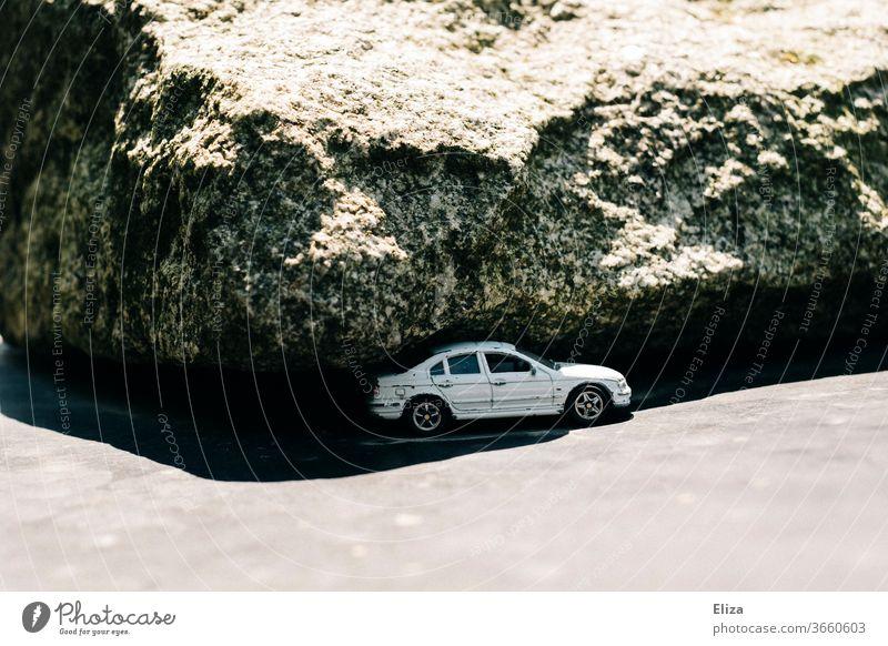 Ein Auto unterm Felsen Fahrzeug Sonne Schatten eingeklemmt gefährlich karg weiß bedrohlich Notlage Spielzeugauto PKW Panne Parken Parkplatz Verkehrsmittel Natur