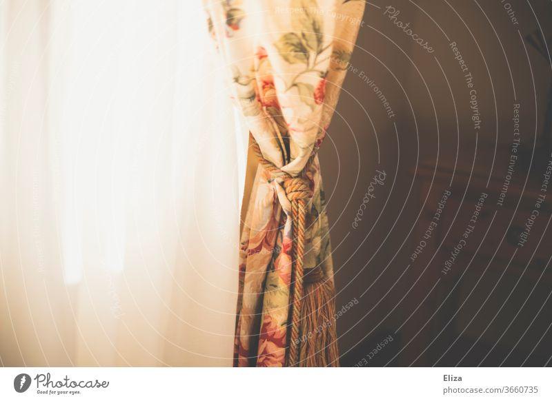 Ein geblümter Vorhang im Sonnenlicht Vorhänge Fenster Gardinen Blumenmuster Sonnsnschein Licht durchlüften Wohnung Fensterbrett hell romantisch matt