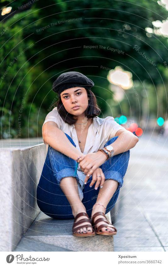 Junge Frau sitzt und schaut in die Kamera Straße Porträt Großstadt Kaukasier schön jung Menschen Person Mode Mädchen attraktiv im Freien Schönheit urban
