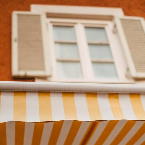 Gelb Weiß gestreifte Markise an einer hübschen Fassade gelb weiß freundlich Altbau Fenster gebäude Haus Altstadt Sonnenschutz Geschäft