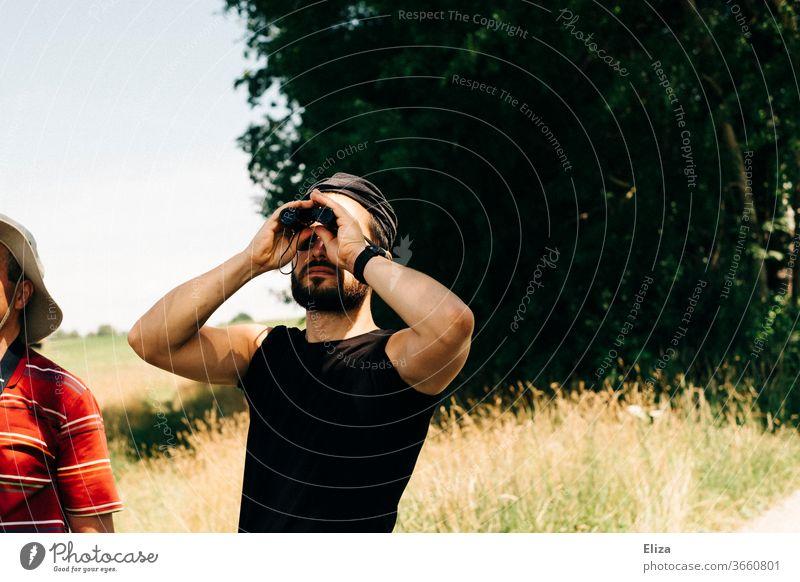Ein Mann beobachtet etwas mit dem Fernglas bei einem Auflug in der Natur beobachten Ferne Ausflug Abenteuer Aussicht entdecken Landschaft Tourismus Vögel