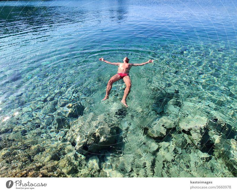 Der Mensch entspannt sich im Urlaub, schwebt im ruhigen, türkisfarbenen Meer. Im Wasser treiben Sommer Schwimmen & Baden Ferien & Urlaub & Reisen Strand