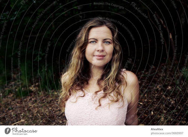 Nahes Portrait einer jungen Frau vor einem Wald lockig Reinheit Glück Schönes Wetter Ausflug Erwartung Sonnenlicht Freude Nahaufnahme feminin Tag