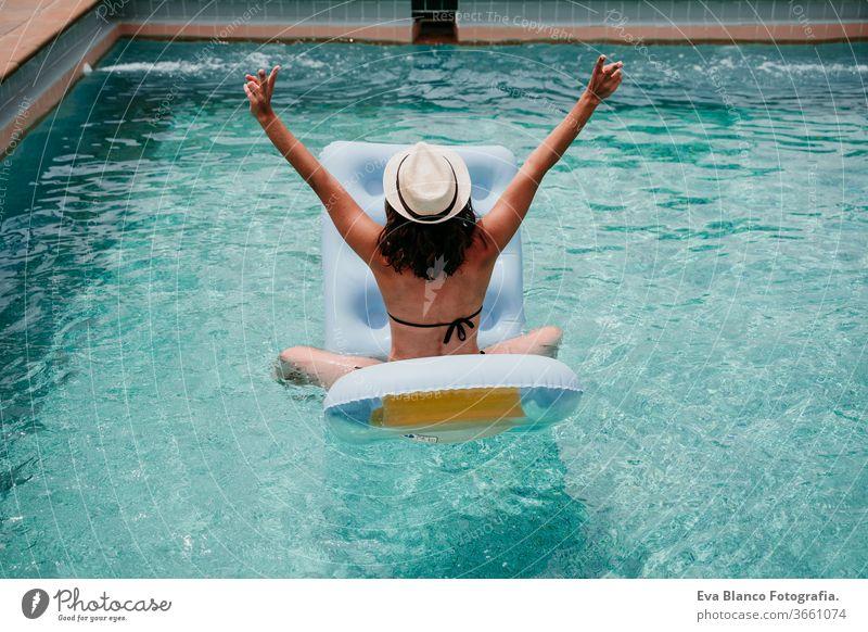 glückliche Frau auf dem Schlauchboot, die Spaß hat. Sommerzeit. Rückansicht Schwimmbad aufblasbar Blauwasser sich[Akk] entspannen Hut Glück Schwimmsport sexy