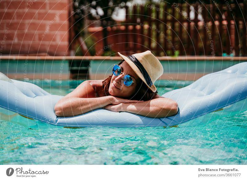 glückliche Frau auf dem Schlauchboot, die Spaß hat. Sommerzeit. Schwimmbad aufblasbar Blauwasser sich[Akk] entspannen Hut Glück Schwimmsport sexy Lifestyle