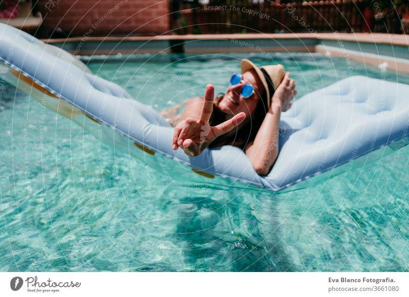 glückliche Frau auf dem Schlauchboot, die Spaß daran hat, mit den Fingern V-Zeichen zu machen. Sommerzeit. v-Zeichen Glück Lächeln Schwimmbad aufblasbar