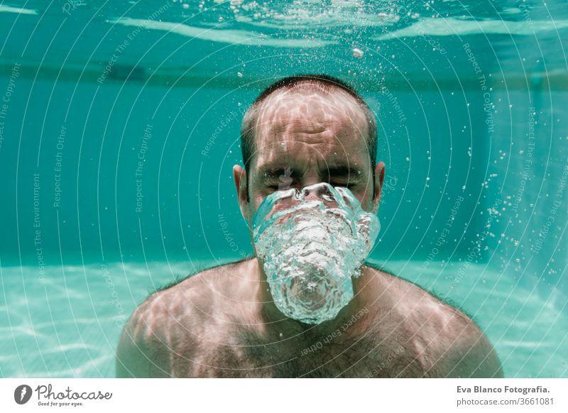 junger Mann taucht unter Wasser in einem Pool und macht Seifenblasen, Sommer und Spaß Schwimmsport Blasen Kaukasier Sinkflug Lifestyle übersichtlich Gesundheit