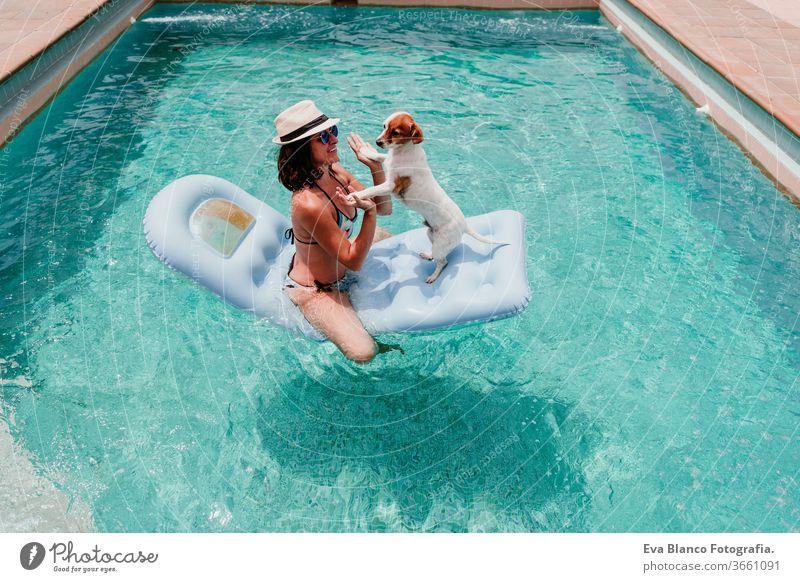 glückliche Frau und Hund in einem Pool, die Spaß haben. Hund sitzt auf einem Schlauchboot und spielt mit seinem Besitzer. Sommerzeit Schwimmbad aufblasbar