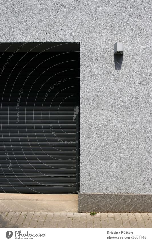 garagentor und graue fassade mit lampe hauswand rolltor mauer einfahrt strahler außenbeleuchtung gebäude architektur fassadengestaltung struktur textur schwarz