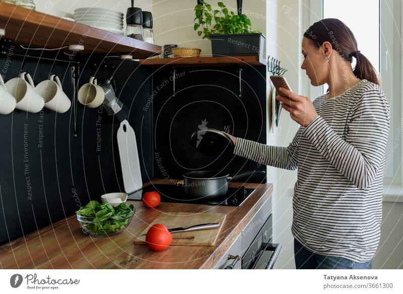 Frau telefoniert beim Kochen Essen zubereiten Küche Telefon heimwärts Lifestyle Lebensmittel Gesundheit Mahlzeit Haus Smartphone Mobile Beteiligung frisch