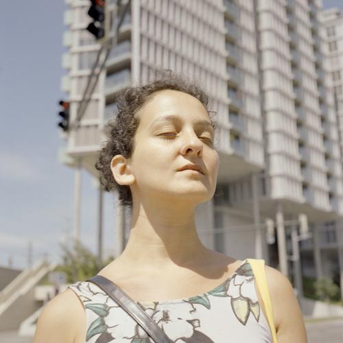 Junge Frau genießt Sonnenstrahlen während einer Pause. Konzept der Kontemplation und Gelassenheit. Gedreht auf analogem Mittelformatfilm Porträt jung Schönheit