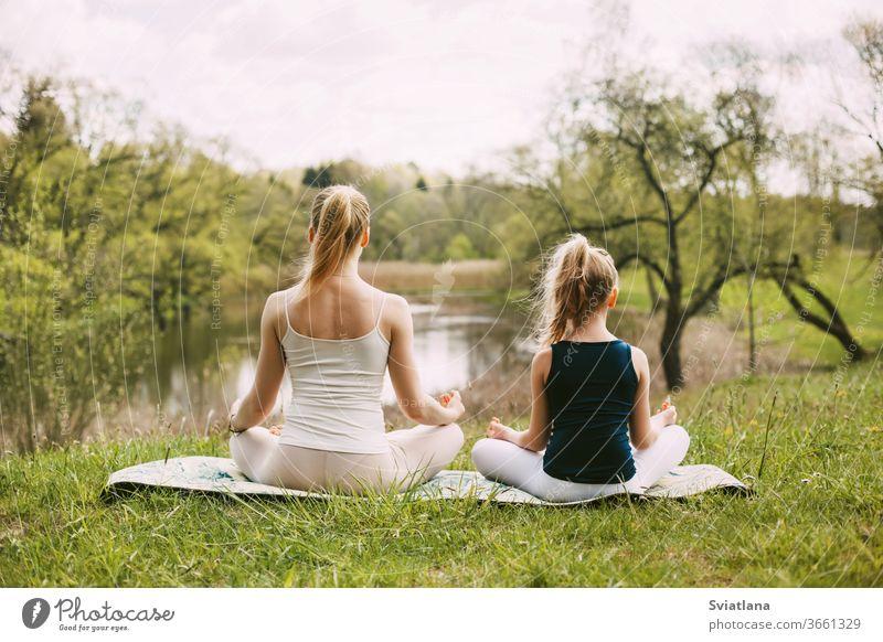 Mutter und Tochter sitzen in der Lotus-Position im Garten. Die Familie praktiziert Yoga im Freien. Rückansicht, Platz für Text Meditation Lotos Zusammensein