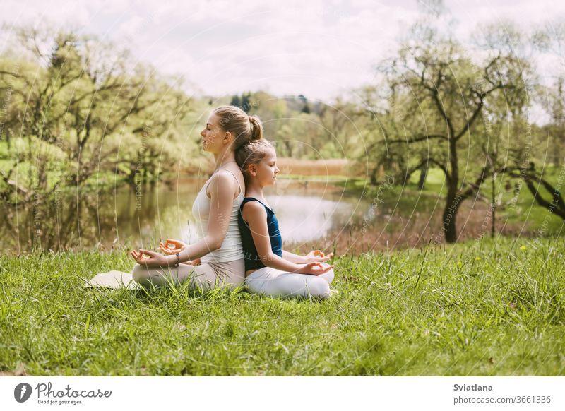 Eine schöne junge Frau und ein blondes Mädchen meditieren in der Lotus-Position. Familienurlaub, Meditation. Seitenansicht, Platz für Text Yoga im Freien Lotos