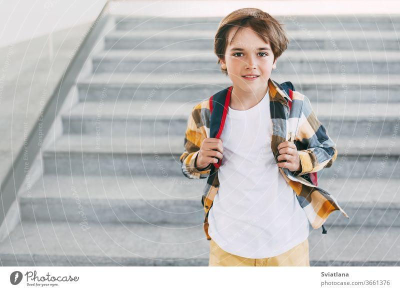 Ein glücklicher Junge mit einem Rucksack steht auf den Stufen vor dem Eingang der Schule und lächelt wunderschön. Beginn des neuen Schuljahres nach den Sommerferien. Zurück zur Schule
