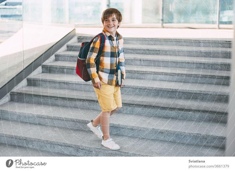 Ein glücklicher Junge mit einem Rucksack und einem Buch geht zur Schule. Beginn des neuen Schuljahres nach den Sommerferien. Zurück zur Schule Kind Rücken