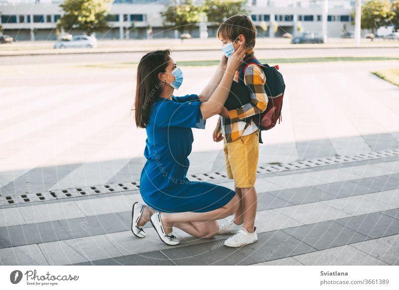 Mama setzt einem Kind eine Maske auf und begleitet es zur Schule oder in den Kindergarten. Ein Junge mit einem maskierten Rucksack während eines Coronavirus. Seitenansicht