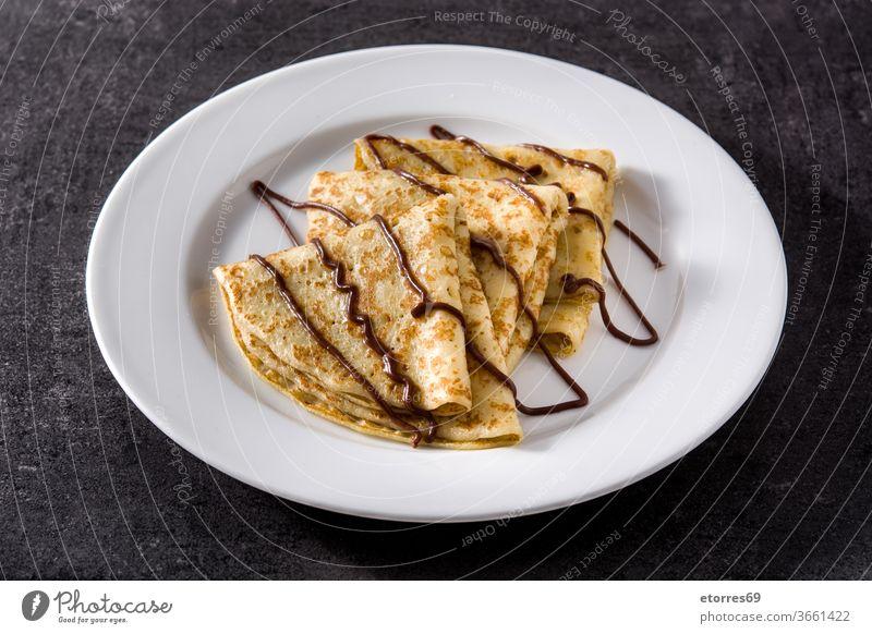 Süße Crêpes mit Schokolade auf schwarzem Hintergrund blinis Frühstück Kakao lecker Dessert Teigwaren Lebensmittel frisch selbstgemacht Gebäck Teller Rezept