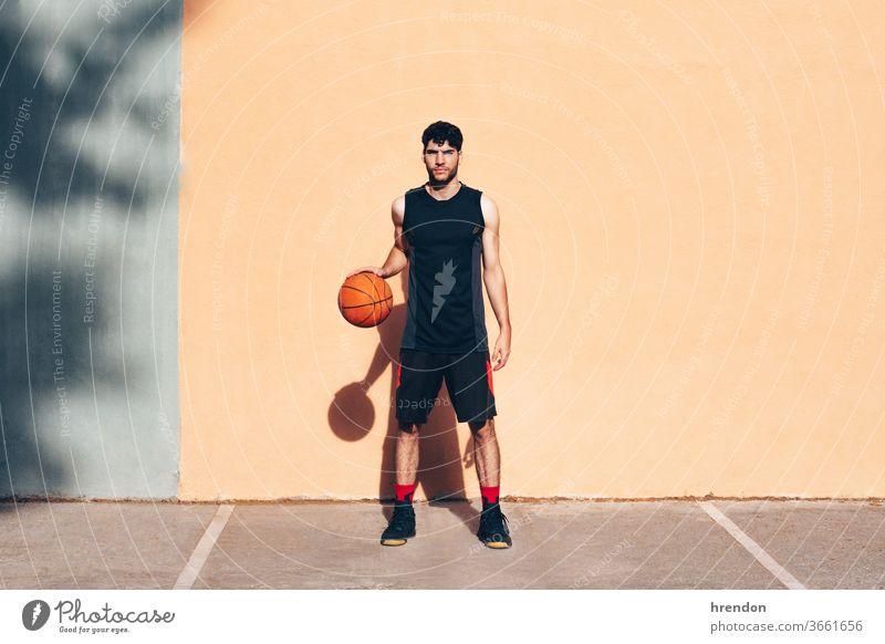 Basketballspieler mit dem Ball vor einer Wand Sport Konkurrenz Spiel sportlich wettbewerbsfähig spielen Spielen Übung männlich trainiert. anstrengen Hobby