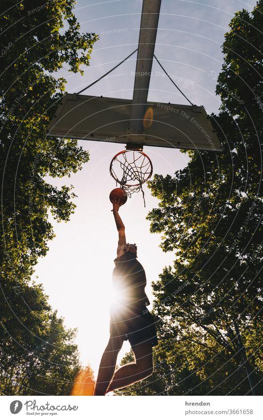 Basketballspieler beim Dunking Sport Konkurrenz Ball Spiel sportlich wettbewerbsfähig spielen Spielen Übung männlich trainiert. anstrengen Hobby Streichholz