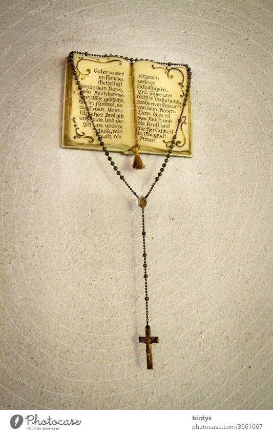 Ein Rosenkranz hängt an einem christlichen ,aufgeschlagenen Gebetsbuch mit dem Vaterunser - Gebet Bibel Christentum Religion und Glaube Katholizismus katholisch