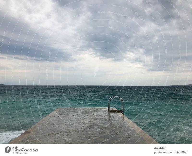 Schwimmen im Sturm wellen Wellen Meer Wasser Küste Strand Wind Wolken Gischt Himmel Außenaufnahme Menschenleer Natur Farbfoto Horizont Unwetter Brandung Tag