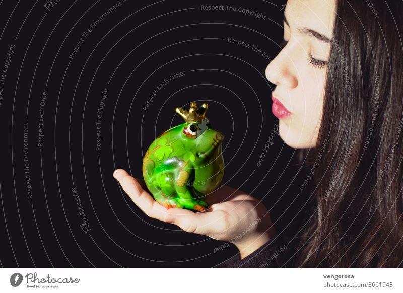 Nahaufnahme eines jungen Mädchens, das eine Froschskulptur vor schwarzem Hintergrund küsst Küssen Kuss Teenager Teenager-Mädchen Teenagermädchen nur ein Mädchen
