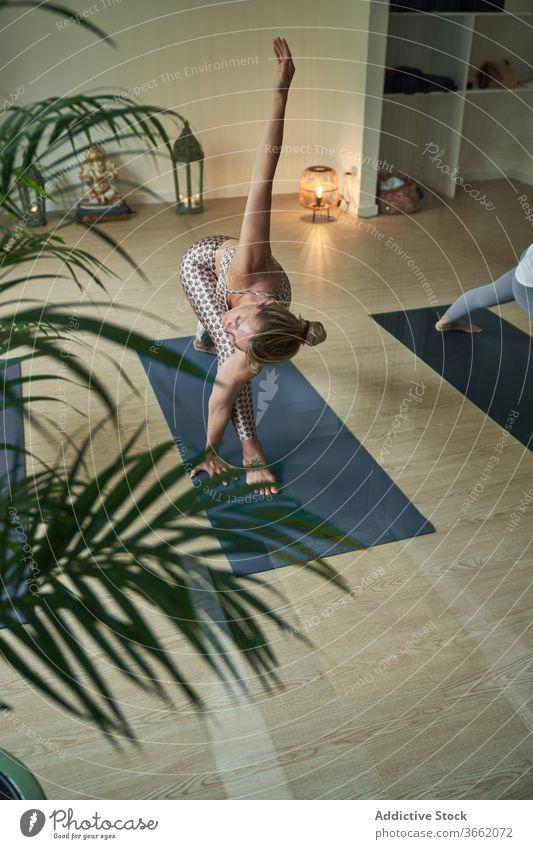 Konzentrierte Frau führt im Studio eine Yoga-Asana an der Longe mit ausgestrecktem Arm aus üben Atelier Ausfallschritt mit nach oben gestrecktem Arm beweglich