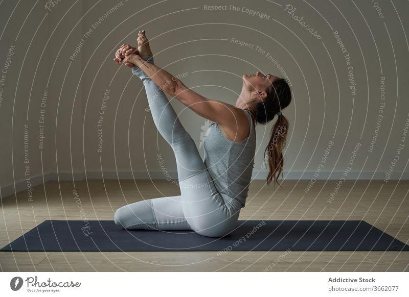 Fokussierte Frau, die Krauncasana Dehnungsyoga-Pose ausführt üben Yoga Atelier Reiher beweglich Windstille Wohlbefinden Gleichgewicht Harmonie Wellness passen