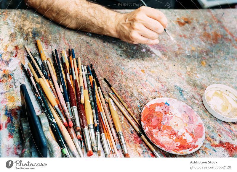 Künstlerhand mit Pinsel über der Arbeitsfläche Pinselblume Arbeitsplatte mehrfarbig Palette Farbe zeichnen kreativ Kunstwerk Beruf Pigment Hand Wasserfarbe