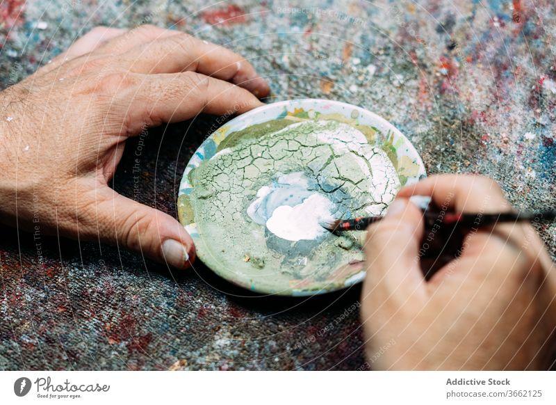Fokussierter Künstler beim Mischen von Farben in einer Palette Mischung mischen Kunst Werkstatt Kleinunternehmen Konzentration Pigment Atelier Beruf Wasserfarbe