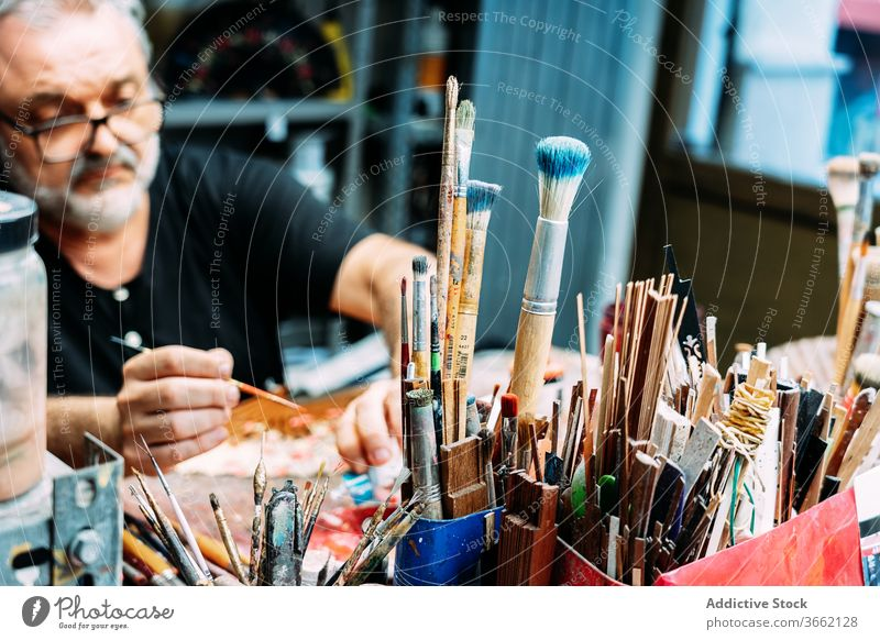 Männlicher Künstler arbeitet hinter einer Reihe verschiedener Pinsel Pinselblume Kunst Designer Arbeitsplatz Atelier Sammlung Kleinunternehmen Skizze Fokus