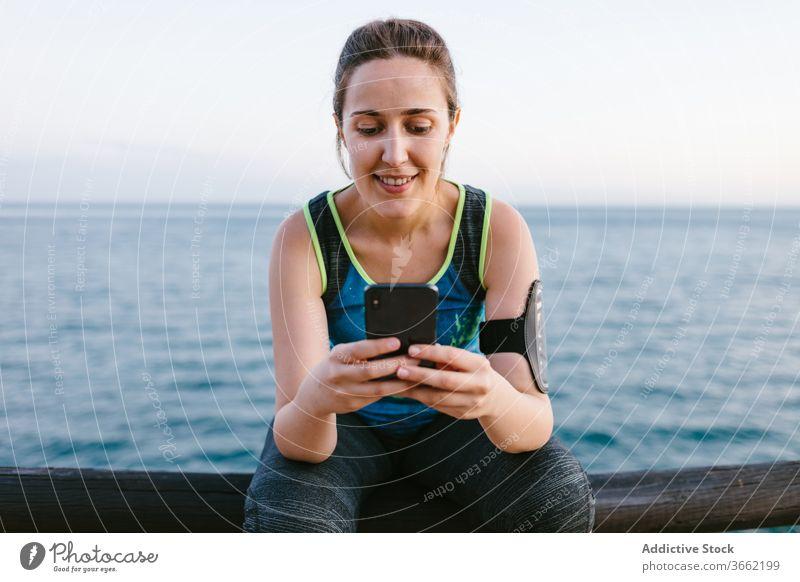 Lächelnde Frau in Sportkleidung mit Smartphone am Meer Sportlerin Stauanlage Browsen sich[Akk] entspannen Training MEER Sportbekleidung benutzend Fitness