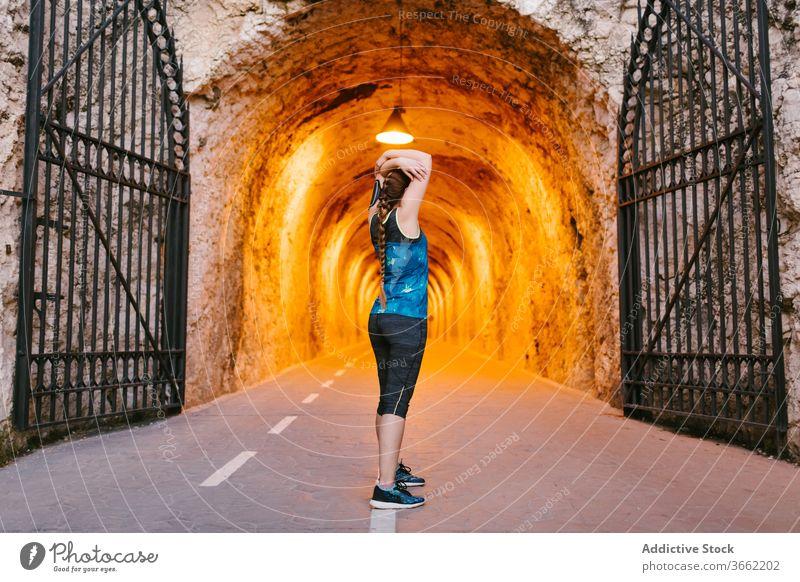 Sportlerin, die während des Trainings im Tunnel die Arme streckt Dehnung Aufwärmen Übung Armbinde Stollen Wand rau Sportbekleidung Athlet Gesundheit passen