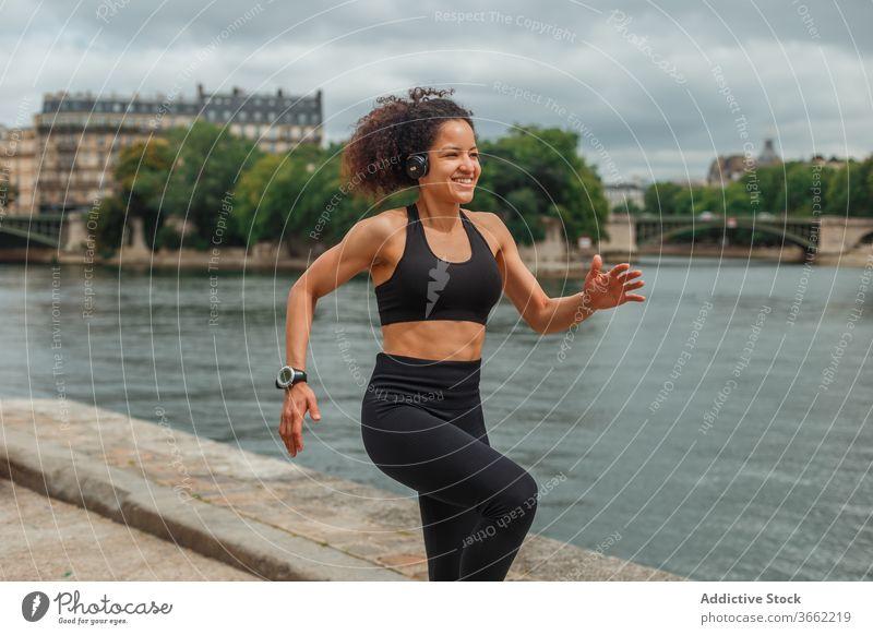 Fröhliche ethnische Sportlerin beim Headset-Training am Stadtfluss Athlet zuhören Musik intelligente Uhr Energie Fluss benutzend Gerät Apparatur Großstadt