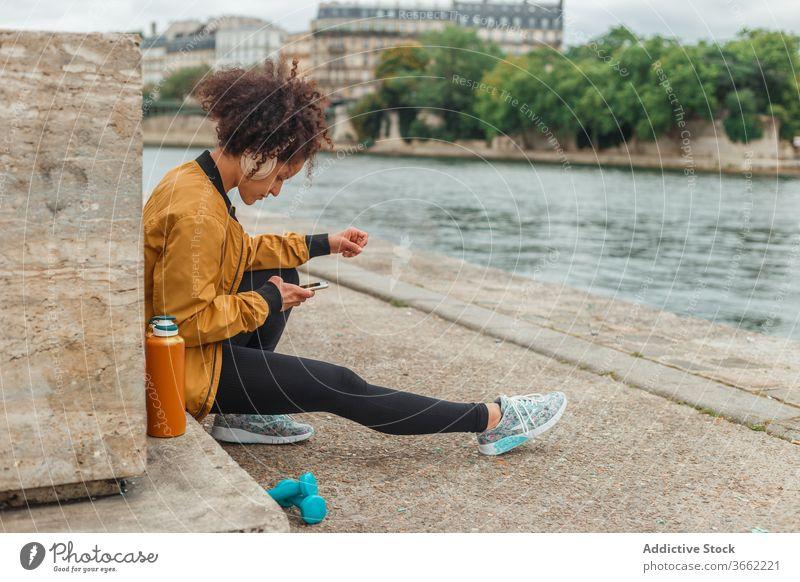 Sportlerin mit Headset nutzt Social Media auf Smartphone nach dem Training Kopfhörer soziale Netzwerke plaudernd Internet Pause Stauanlage Fluss benutzend
