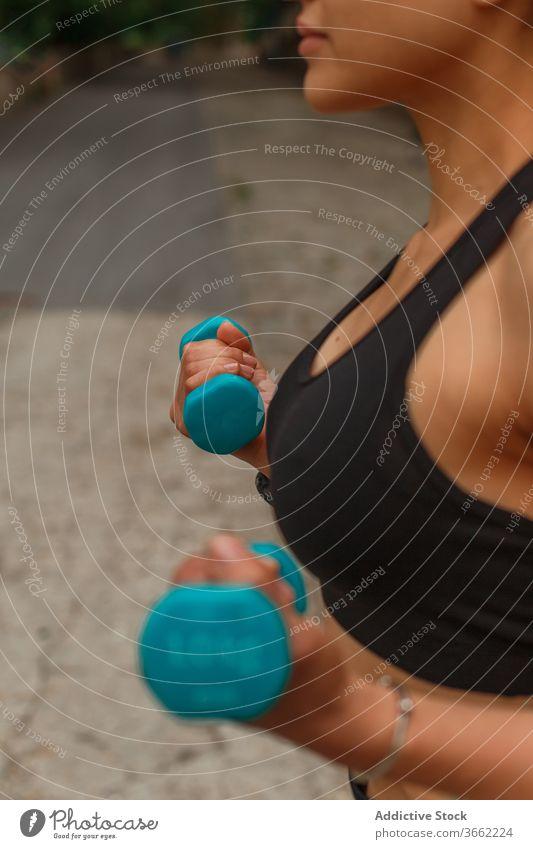 Fitnesstraining für ethnische Sportlerinnen mit Kurzhanteln auf der Böschung während des Trainings Kniebeuge Gleichgewicht erreicht Arme Straßenbelag Dehnung