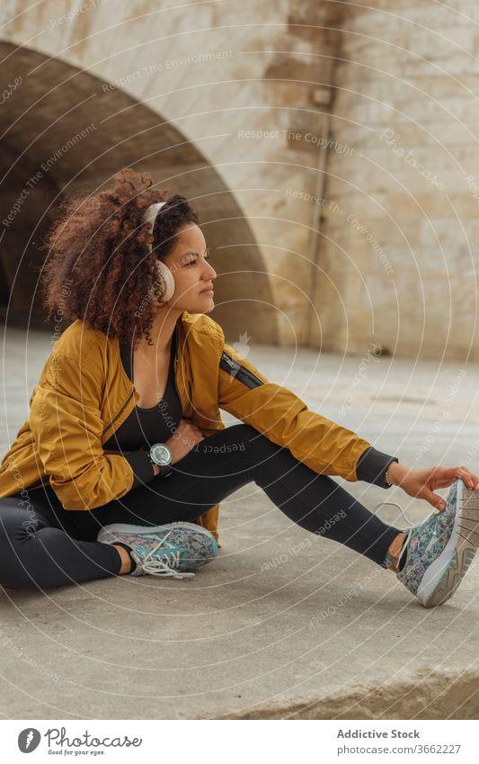 Ethnische Sportlerin mit Kopfhörern streckt Bein auf Bürgersteig in der Stadt Headset Dehnung Übung Training Sportbekleidung Straßenbelag urban benutzend Gerät