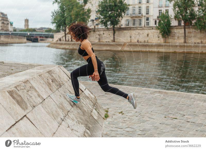 Nicht erkennbare ethnische Sportlerin trainiert auf einem Damm in der Nähe des Stadtflusses Training Aufwärmen Aufstieg Podest Stauanlage Herz Teich Energie