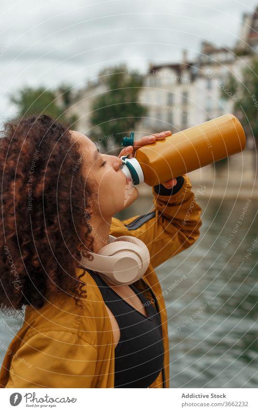 Durstige ethnische Sportlerin trinkt Wasser, nachdem sie in der Nähe eines Flusses trainiert hat trinken Flasche Headset Sportbekleidung Pause Baum benutzend