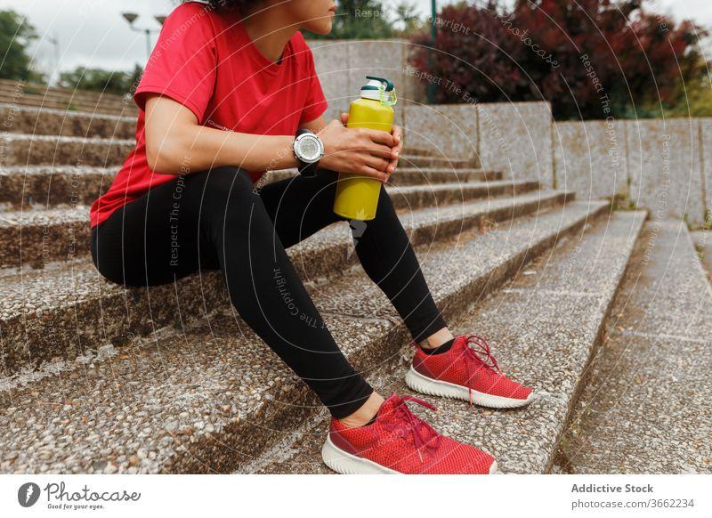 Durstige ethnische Sportlerin trinkt nach dem Training Wasser auf der Treppe trinken Thermoskanne Sportbekleidung Pause Hydrat Augen geschlossen