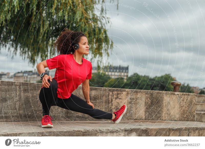 Ethnische Sportlerin mit Kopfhörer, die beim Aufwärmen im Freien ihr Bein streckt Kniebeuge Dehnung Training Übung Drahtlos zuhören Musik Headset beweglich