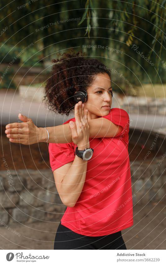 Ethnische Sportlerin mit Headset, die während des Trainings im Park den Arm streckt Athlet Dehnung Arme intelligente Uhr Übung zuhören Musik Drahtlos erreicht