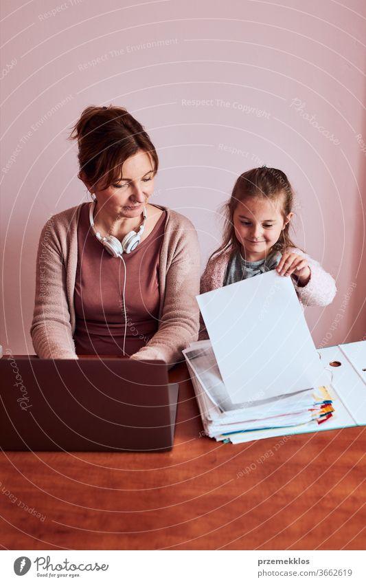 Frau bei der Arbeit, die während eines Videochat-Telefongesprächs mit einem Laptop von zu Hause aus ihre Arbeit aus der Ferne erledigt. Frau sitzt am Schreibtisch vor dem Computer und schaut mit Kopfhörern und Smartphone auf den Bildschirm, während ihre Tochter herumspielt. Konzept des Remote-Arbeitens