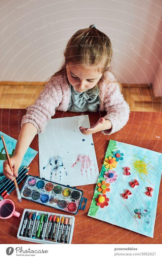 Kleines Mädchen im Vorschulalter, das mit bunten Farben und Buntstiften ein Bild malt. Kind, das während eines Kunstunterrichts im Klassenzimmer Spaß beim Malen eines Bildes hat